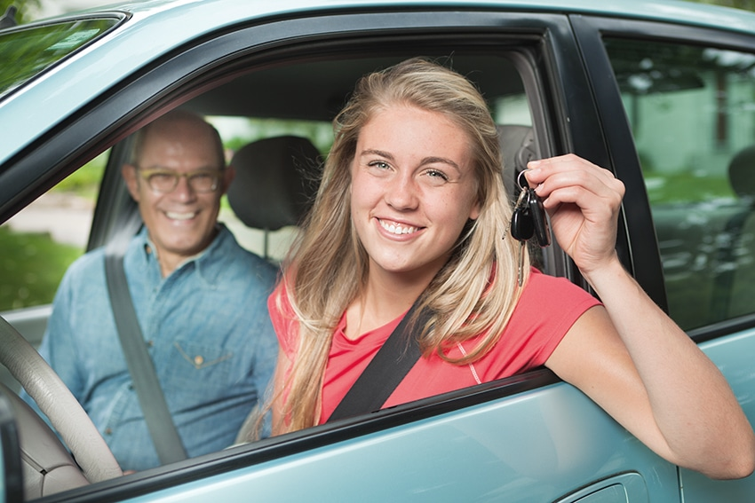 Mädchen hält Schlüssel in die Kamera. Sitzt neben ihrem Fahrlehrer im Auto.