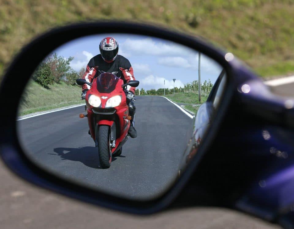 Motorradfahrer nähert sich Auto im Seitenspiegel