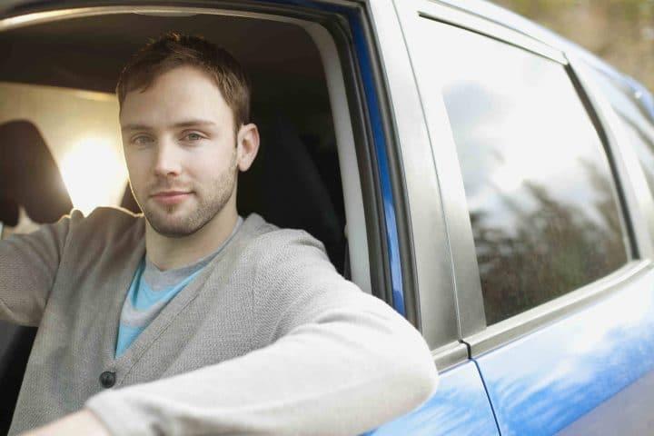 Junger Mann sitzt in einem Auto.