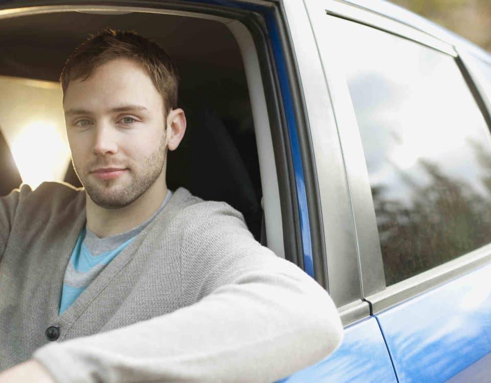Junger man als Autofahrer in blauem Auto