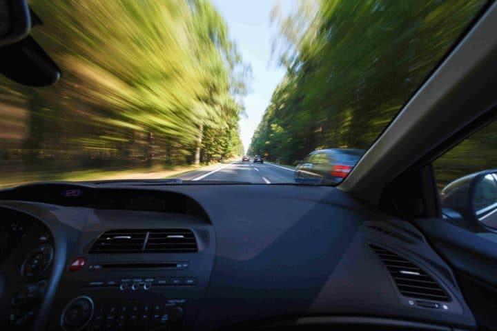 Autos fahren auf Straße umgeben von Bäumen