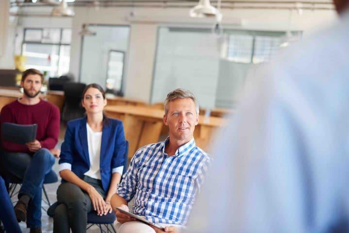 Eine Frau und ein Mann hören einer sprechenden Person zu.