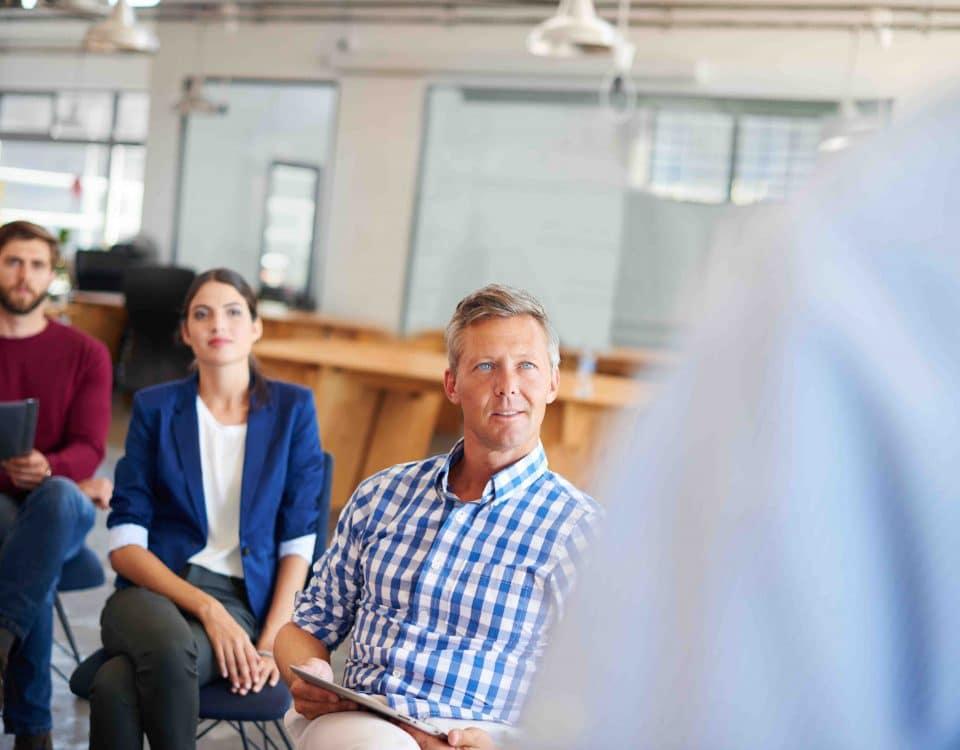 Teilnehmer hören dem Vortragenden zu
