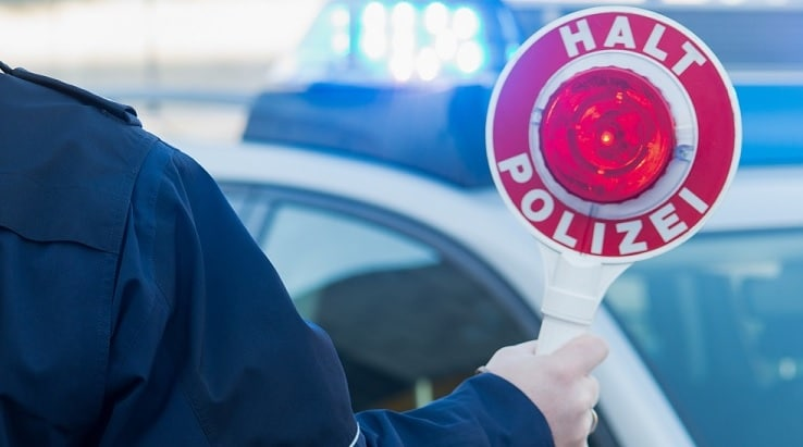 Polizist mit Kelle steht vor Auto mit Blaulicht.