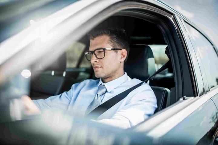 Mann sitzt am Steuer eines Firmenautos.