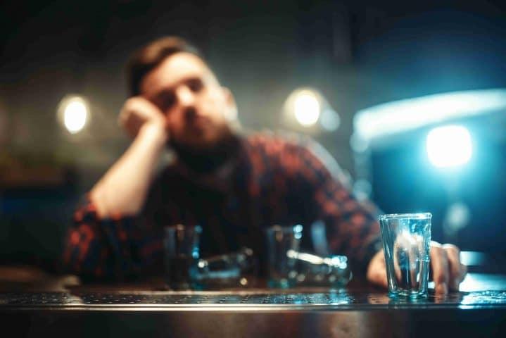 Alkoholisierter Mann sitzt mit Getränk an der Bar.