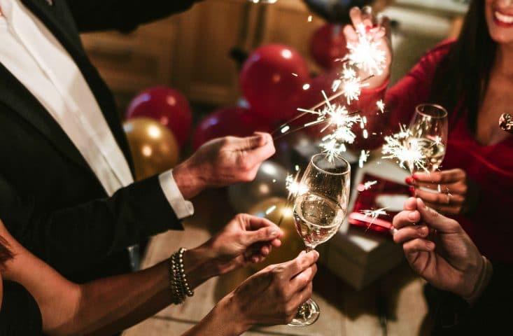Feiernde stoßen mit Prosecco und Sprühkerzen an.