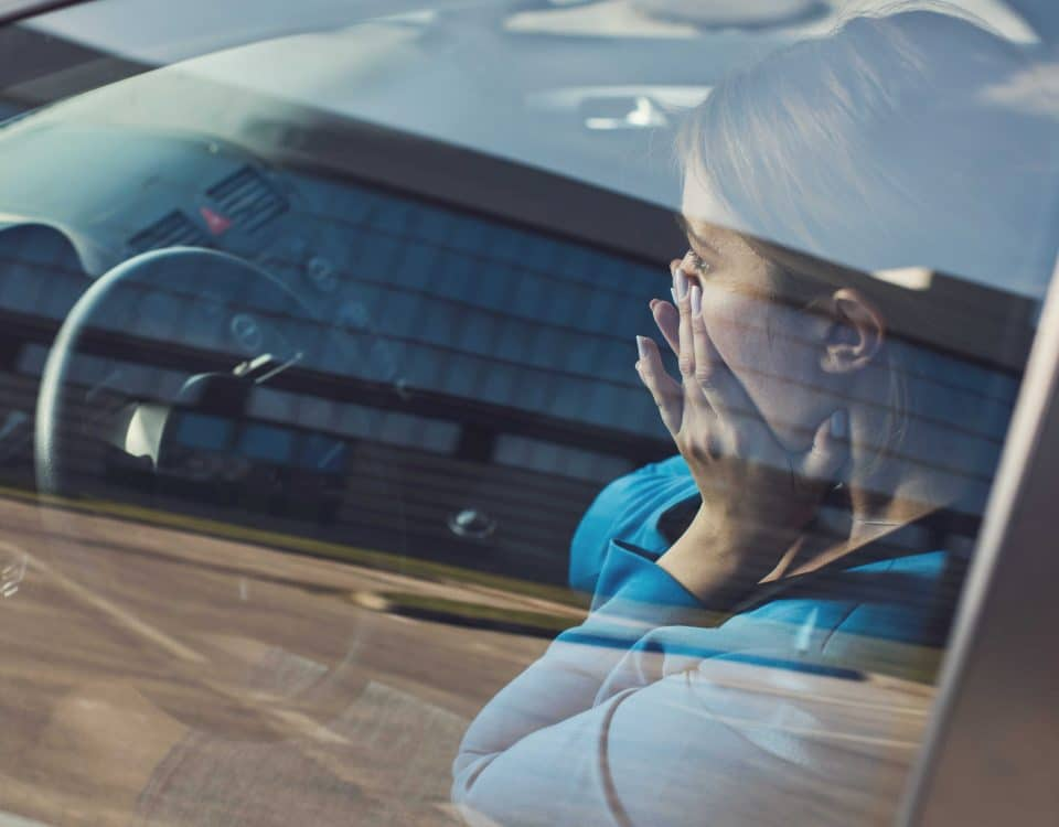 Frau sitzt mit Angst beim Autofahren hinter dem Steuer.