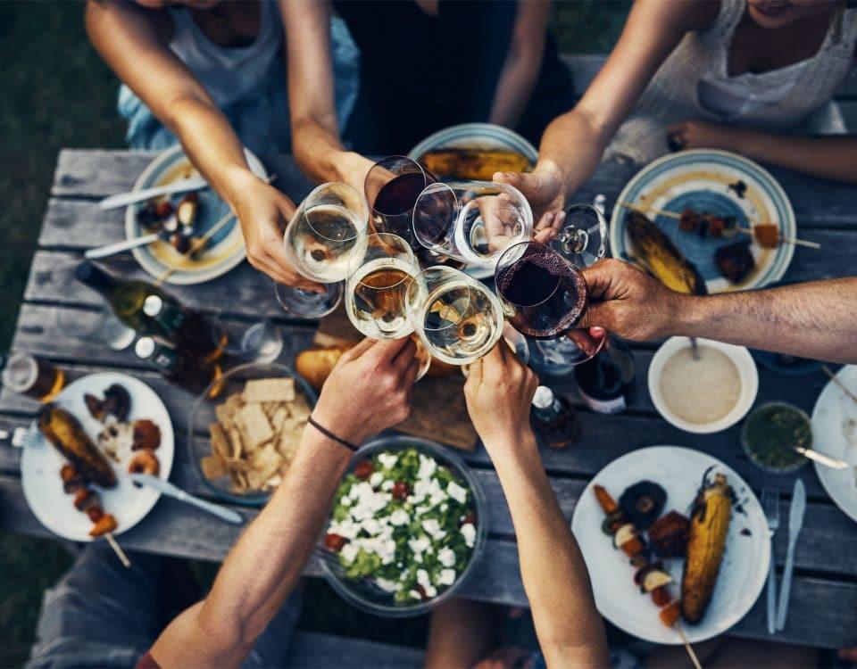 Das Bild zeigt mehrere Hände mit Weingläsern, die anstoßen.