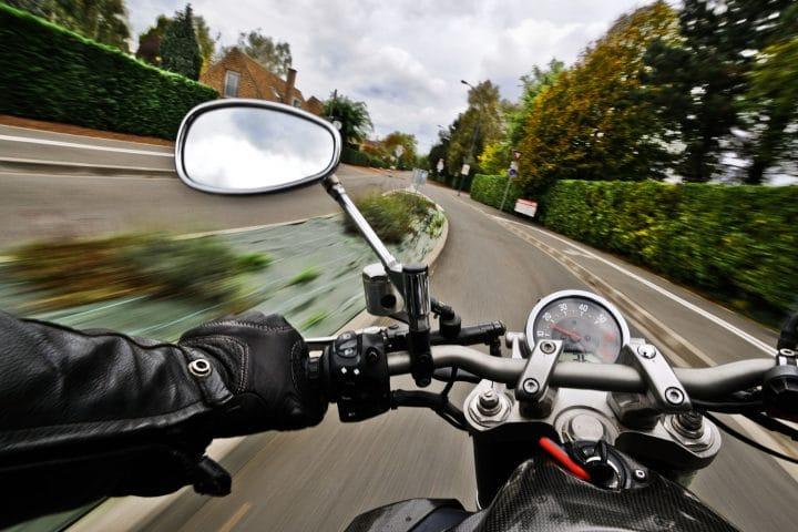 Das Bild zeigt einen schnellen Motorradfahrer in einer Kurve.